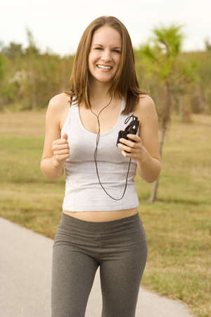 Attractive female jogger outside listening to music