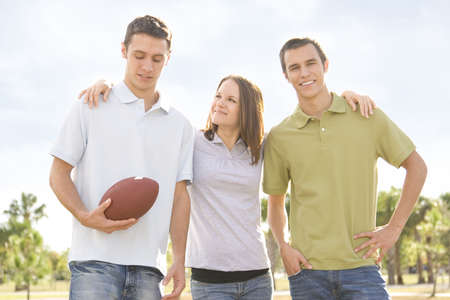 Attractive young people outside holding an american football photo