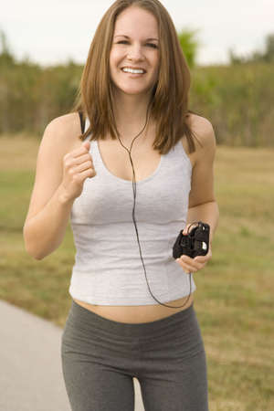 Attractive female jogger outside listening to music Stock Photo - 6089550