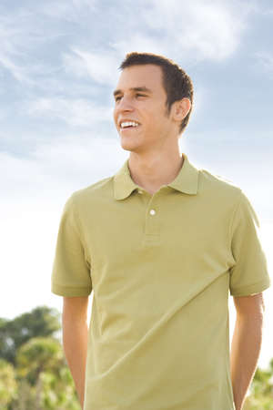 Young attractive casual man outside looking to side of camera photo
