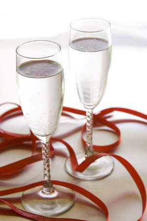 Champagne glasses on silver background with ribbon.