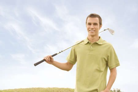 People against blue sky with golf clubs photo