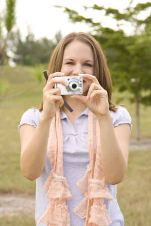 Attractive young woman outside with a camera Stock Photo