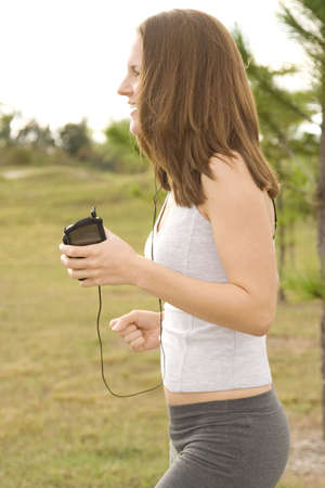 Attractive female jogger outside listening to music Stock Photo - 6111714
