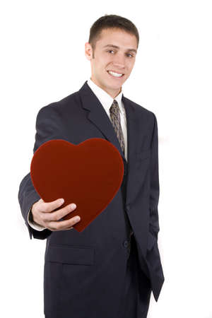 Young attractive man on white holding a red valentine. photo