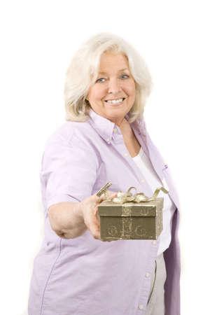 Beautiful mature woman holding a gift on white photo