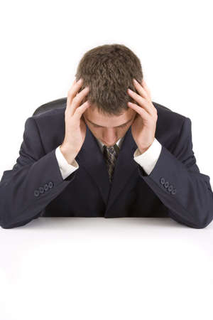 Stressed businessman sitting at his desk with head in hands Imagens