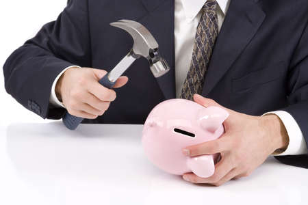 Young businessman on white with a piggy bank and hammer.