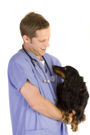 Veterinarian on white holding a black dog.
