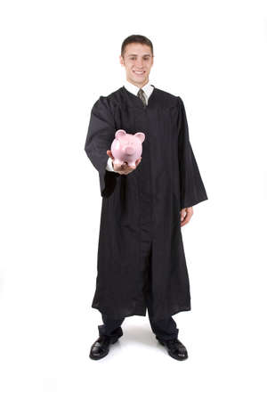 Young graduate in cap and gown holding a piggy bank. photo
