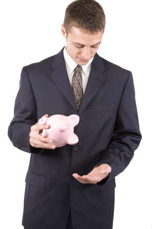 Young businessman looking for more money from a piggy bank photo