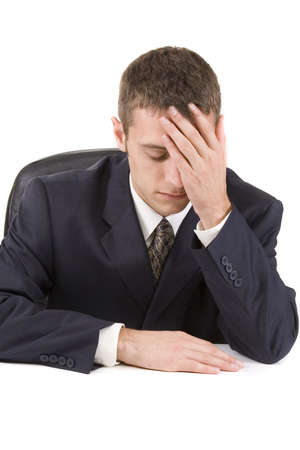Stressed businessman sitting at his desk with head in hands Stock Photo