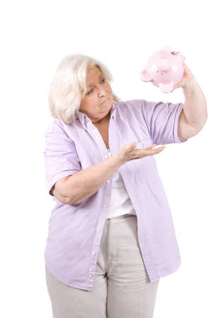 Beautiful mature woman with a piggy bank on white. photo