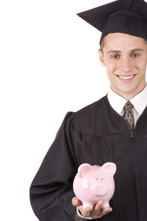 Young graduate in cap and gown holding a piggy bank. Stock Photo