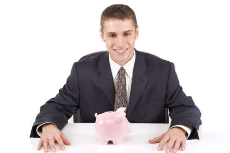 Young businessman at table with a piggy bank photo