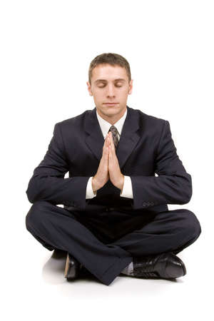 Young businessman in yoga position on white photo