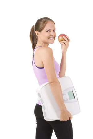 Woman on white holding an apple and scale photo