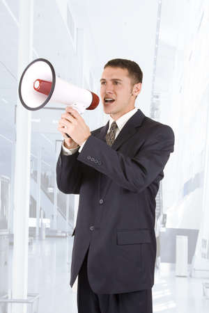 Young attractive businessman shouting into a megaphone. Stock Photo - 6450195