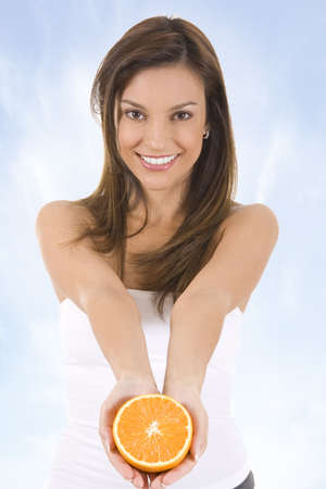 Young woman against blue sky with an orange. photo