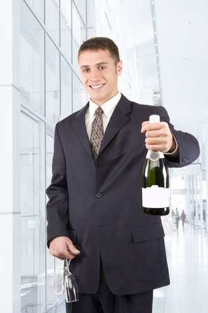 Attractive young man holding champagne and flutes photo