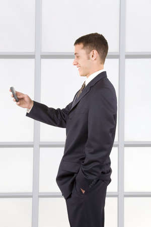 Young attractive businessman texting on a cell phone. photo