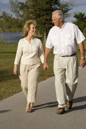 Attractive senior couple walking together in a park photo