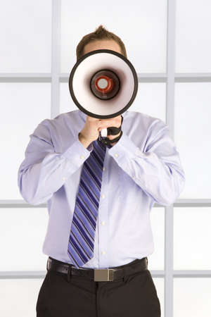 Young attractive businessman shouting into a megaphone. Stock Photo - 6474602