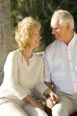 facial expression: Happy senior couple sitting in a park.