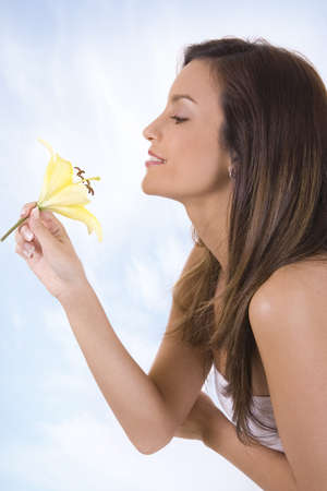 Young beautiful woman with a flower against sky photo