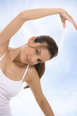 Young woman against a blue sky in a fitness pose photo