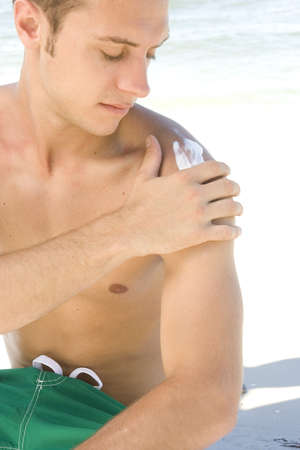 Young man at the beach applying sunblock photo
