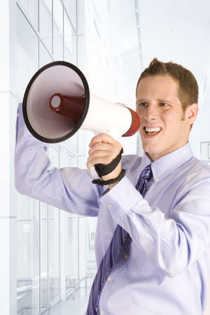 Young businessman shouting into a megaphone photo
