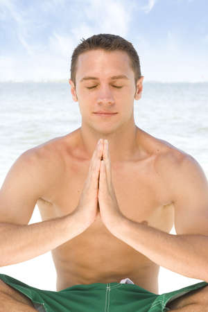 Young attractive man meditating at the beach. photo