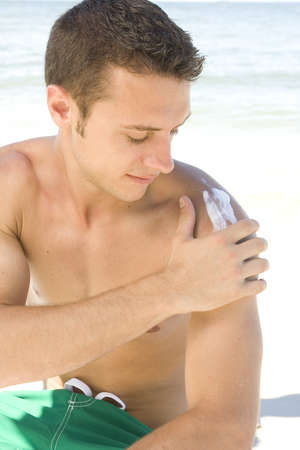 Young man at the beach applying sunblock