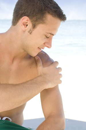 Young man at the beach applying sunblock Stock Photo - 7556654