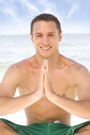 Young attractive man meditating at the beach. Stock Photo - 7556673