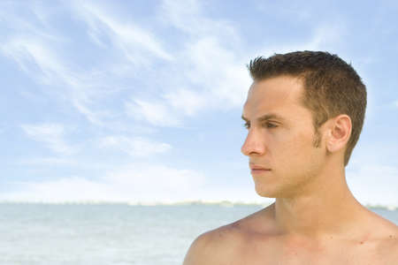 Attractive young man at the beach in green trunks photo