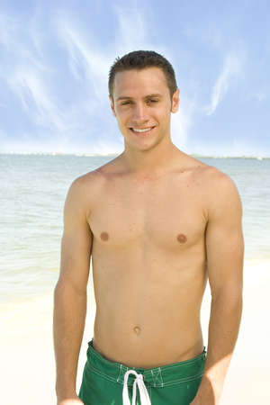 Attractive young man at the beach in green trunks Stock Photo - 7556658