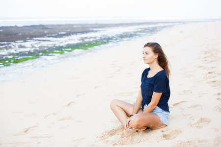 Beautiful woman sits in lotus position on white sand.
