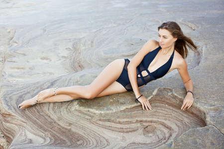 Beautiful woman in black swimsuit lies on sand seashore.