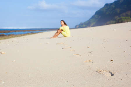 Footprints on the sand. Unfocused girl sitting on the beach Stock Photo