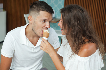 young couple in white clothes have fun in the cafe. The girl feeds the guy ice cream cone Imagens