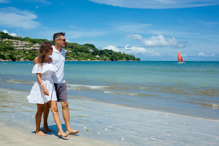 Beach couple walking on romantic travel honeymoon vacation summer holidays romance. Young happy lovers, woman and man holding hands embracing outdoors. Banco de Imagens
