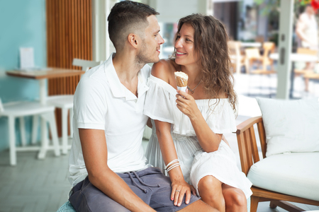 portrait of a smiling young couple in white with ice cream cone. Man and woman looking to each other. Cafe, interior