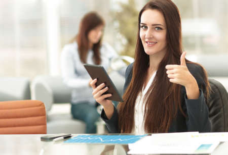 Happy confident entrepreneur working with a tablet computer gesturing thumbs up looking at camera sitting on a couch at office Stock Photo
