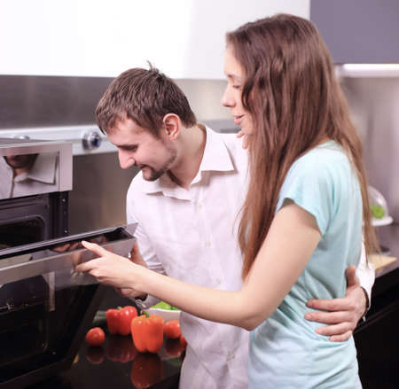 Portrait of happy young couple cooking together in the kitchen.