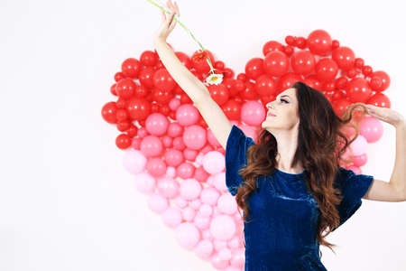 Sexy brunette woman with red heart balloons and flowers Standard-Bild
