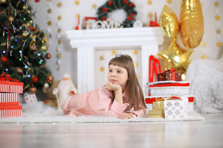 Merry Christmas and Happy Holidays Cute little child girl is decorating the Christmas tree indoors. Standard-Bild