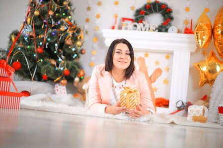Happy young lady with curlu hair gifts by the fireplace near the Christmas tree. New year concept.