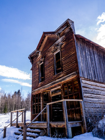two story: Old, olitary, abandoned wooden two story house in winter Editorial